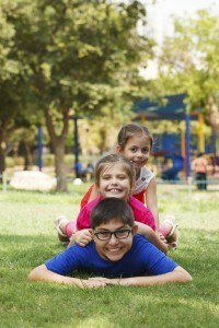 Happy children of three playing piggy back at summer camp