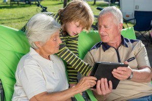 Grandson and his grandparents using digital tablet