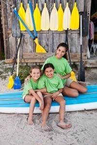 Teenage girl (17 years) with children (8-9 years) sitting on paddle board by water sports equipment center